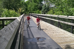 Children Biking on Wooden Bridge