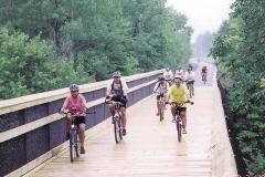 People Biking Over Bridge on the Musketawa Trail